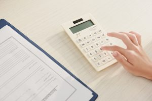 cropped view of woman counting finances on calculator at table with insurance claim form